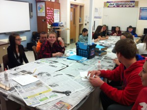 Newspapers scattered on a table while students build bridges