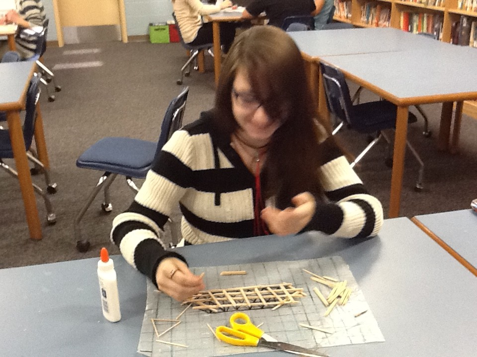 A student smiles as her bridge comes together
