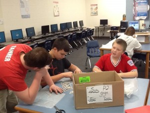 Students retrieve bridge supplies from a box