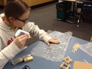 A student aims a glue bottle at her toothpicks